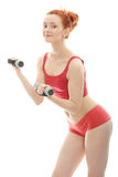 Deaf girl exercising. Beautiful, young, deaf (with hearing aid in ears) redhead exercising with dumb bells Royalty Free Stock Images