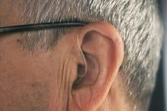 Deaf man hearing aid ear. Deaf senior citizen man wearing modern digital high technology hearing aid in ear stock photography