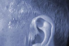 Deaf man hearing aid ear. Deaf senior citizen man wearing modern digital high technology hearing aid in ear stock photos