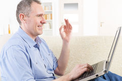 Deaf man using sign language with laptop Royalty Free Stock Images