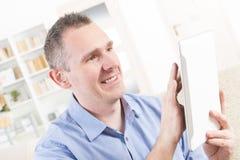 Deaf man using tablet. Smiling Deaf man talking using tablet at home stock photo
