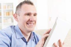Deaf man using tablet. Smiling Deaf man talking using tablet at home stock photography