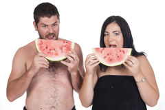 Deaf man and woman eating water melon. Deaf men and women eating water melon dressed in black towels Royalty Free Stock Photos