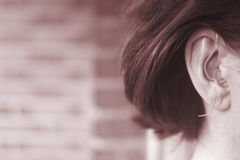 Deaf woman hearing aid ear. Deaf middle aged lady wearing modern digital high technology hearing aid in ear royalty free stock image