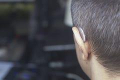 Deaf man hearing aid ear. Deaf middle aged man wearing modern digital high technology hearing aid in ear stock photos
