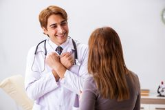 The deaf-mute female patient visiting young male doctor. Deaf-mute female patient visiting young male doctor royalty free stock images