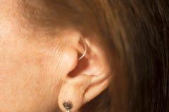 Deaf woman hearing aid ear. Deaf senior citizen lady wearing modern digital high technology hearing aid in ear royalty free stock photography