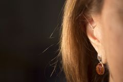 Deaf woman hearing aid ear. Deaf senior citizen lady wearing modern digital high technology hearing aid in ear stock photography