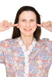 Deaf Senior Woman. Smiling adult woman keeping the ears shut with her fingers, meaning she does not want to hear nothing or she is deaf Royalty Free Stock Photography