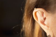 Deaf woman hearing aid ear. Deaf senior citizen lady wearing modern digital high technology hearing aid in ear stock photos