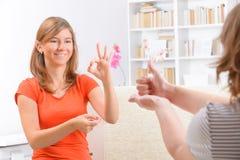 Deaf woman learning sign language. Smiling deaf woman learning sign language royalty free stock photography