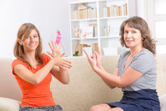 Deaf woman learning sign language. Smiling deaf women learning sign language and talking with her teacher Royalty Free Stock Photo