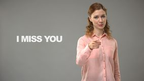 Deaf woman saying miss you in sign language, text on background, communication. Stock footage stock video