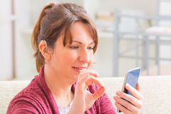 Deaf woman using sign language on the smartphone. Smiling Deaf woman talking using sign language on the smartphone's cam Stock Photo