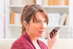 Deaf woman using sign language on the smartphone. Smiling Deaf woman talking using sign language on the smartphone's cam Royalty Free Stock Image
