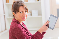 Deaf woman using tablet. Smiling Deaf woman using tablet at home Stock Image