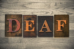 Deaf Wooden Letterpress Theme. The word DEAF theme written in vintage, ink stained, wooden letterpress type on a wood grained background Royalty Free Stock Photography