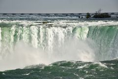 The Deafening and Exhilarating Niagara Falls. The Niagara River is a torrent plunging over the brim of the Horseshoe Falls. It`s a spectacular sight so near to royalty free stock photo