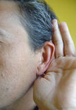 Deafness. Close up sight of the gesture of deafness where you can see an ear and a hand covering it like sound amplifier Royalty Free Stock Images