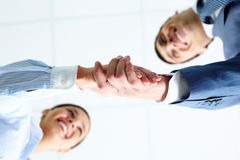 Deal. Below angle of successful associates handshaking after striking deal Royalty Free Stock Image