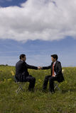 The Deal. Two businessman making a deal with a handshake at the field royalty free stock image