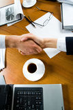 Deal. Close-up of people making a deal with a handshake over the table Stock Image