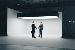 Deal concept. Businessmen shaking hands in modern photo studio interior with professional lightint equipment. Deal concept. 3D Rendering Stock Photos