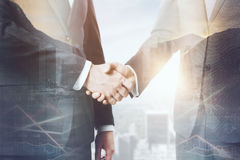 Deal concept. Handshake on abstract city background with forex chart and sunlight. Deal concept. Double exposure Royalty Free Stock Image