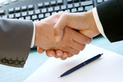 Deal done. Businessmen shaking hands over a desk Stock Photo