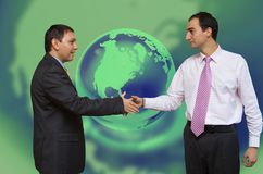 Deal in the financial world. Businessmen shaking hands with blue green global background royalty free stock photography