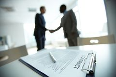 Deal. Image of business contract on background of two employees handshaking Stock Photo