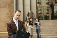The deal is ready to be signed. Business man looking at the camera with his briefcase opened and business ladies talking in the background in front of a building Stock Images