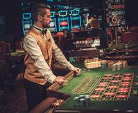 Dealer behind table in a casino stock photo