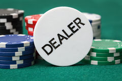 Dealer button and poker chips on a green surface. Royalty Free Stock Image