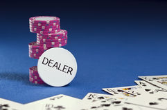 Dealer button, poker chips, playing cards. Stock Image