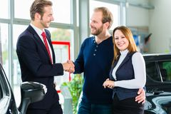Dealer, clients and auto in car dealership. Seller or car salesman and clients or customers in auto dealership presenting the interior decoration of new and used stock photography