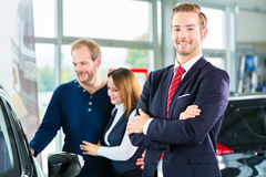 Dealer, clients and auto in car dealership. Seller or car salesman and clients or customers in car dealership presenting the interior decoration of new and used royalty free stock image