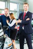 Dealer, clients and auto in car dealership. Seller or car salesman and clients or customers in car dealership presenting the interior decoration of new and used royalty free stock photo