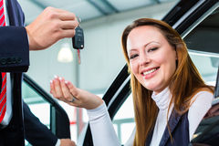 Dealer, female client and auto in car dealership. Seller or car salesman and female client or customer in car dealership presenting the interior decoration of Royalty Free Stock Photo