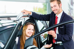 Dealer, female client and auto in car dealership. Seller or car salesman and female client or customer in car dealership presenting the interior decoration of Stock Photography