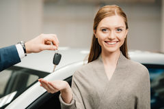 Dealer giving car key to beautiful woman new owner Stock Image