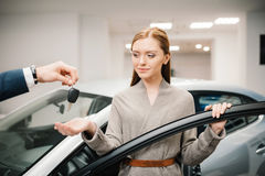 Dealer giving car key to beautiful woman new owner Royalty Free Stock Photos