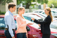 Dealer Giving Car Key To Couple. Side View Of Female Dealer Giving Car Key To Happy Couple Royalty Free Stock Images
