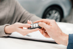 Dealer giving car key to new owner Royalty Free Stock Photos