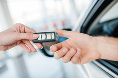 Dealer giving car key to new owner Royalty Free Stock Photography