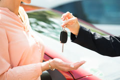 Dealer Giving Car Key To Woman. Close-up Of A Dealer Giving Car Key To Woman Stock Photography