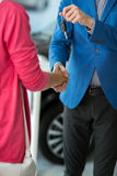 Dealer giving key to new owner. Close up of dealer giving key to new owner and shaking hands in auto show or salon Royalty Free Stock Photos
