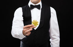 Dealer holding golden poker chip Royalty Free Stock Image