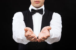 Dealer holding something on palms of his hands. Magic, performance, circus, casino and show concept - casino dealer holding something on palms of his hands stock image