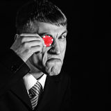 Dealer, man with a red chip - monocular Royalty Free Stock Photos